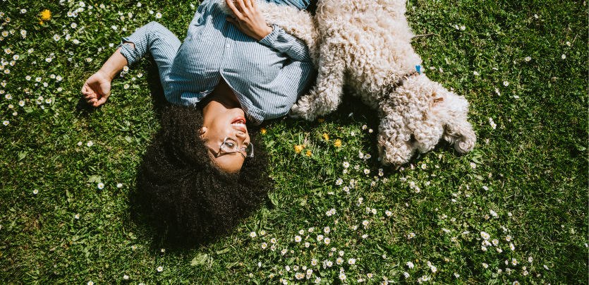 a dog and woman laying on grass